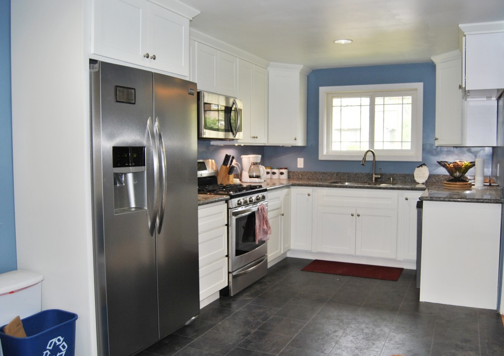 remodeled kitchen stainless steel fridge sink window. white cabinets, gray floor. home improvement. renovation. house reno. | bexbernard.com