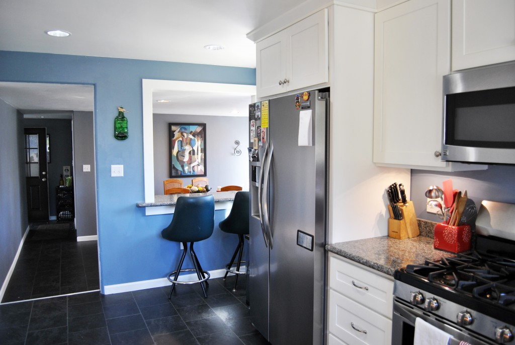 remodeled kitchen with blue walls, granite countertops, white cupboards, slate gray floors, stainless steel fridge, dishwasher, microwave, and gas stove. Undercabinet lighting. | www.bexbernard.com