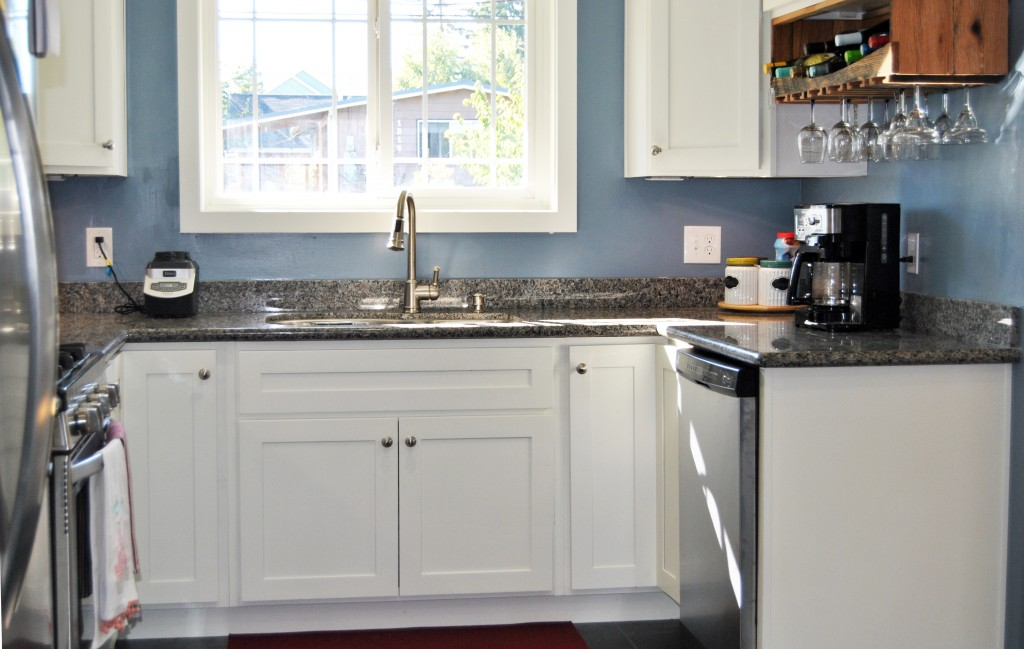 remodeled kitchen with stainless steel dishwasher, two tub sink with a gooseneck faucet, blue walls, granite countertops, white cupboards. Undercabinet lighting. | www.bexbernard.com
