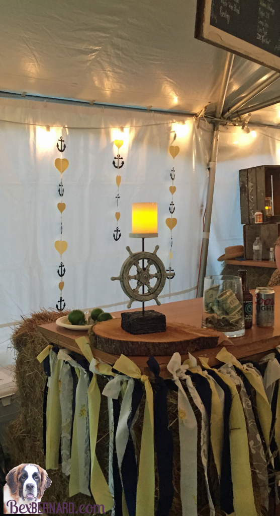 Ship helm bar at a rustic nautical wedding in Pacific Northwest with anchor decorations and hay bales.   bexbernard.com