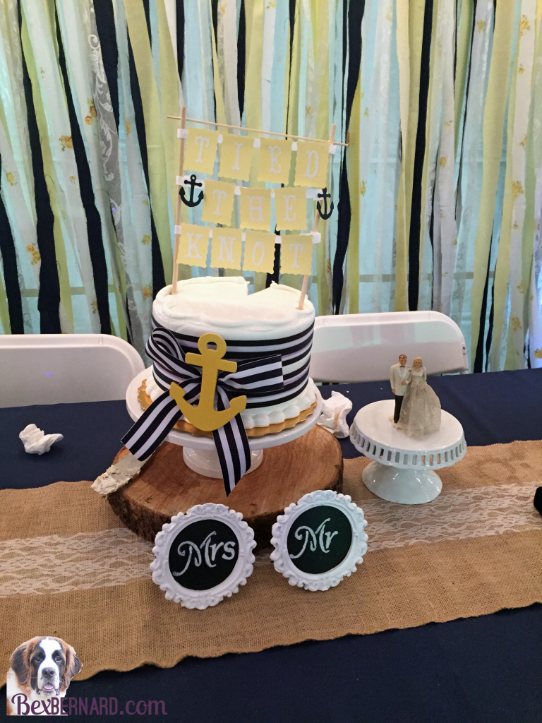 Blue and white striped anchor cake at a rustic nautical wedding in Pacific Northwest with anchor decorations and hay bales. | bexbernard.com