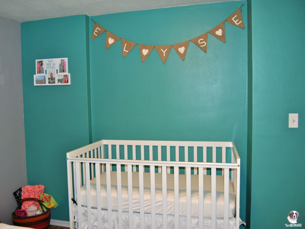 mermaid theme nursery with burlap banner and white crib against teal wall | bexbernard.com