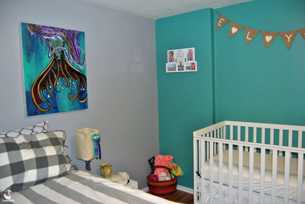mermaid theme nursery with white crib and basket of blankets against teal wall | bexbernard.com