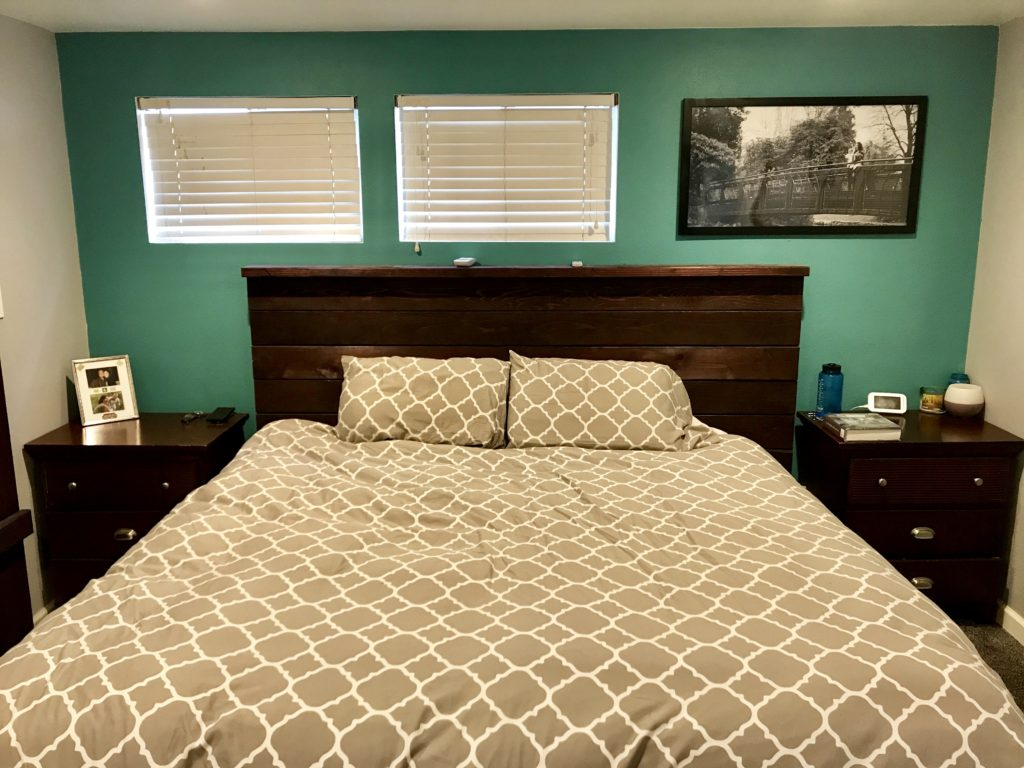 DIY rustic headboard with dark black cherry stain. Gray bedroom walls with teal painted accent wall.